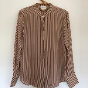 Skjorte med lodrette striber i offwhite og brun. Skjulte knapper foran.