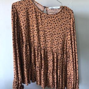 Orange/brunlig bluse med sort blomster mønster fra Zara. Str. S Aldrig brugt, men uden prismærke Køber betaler fragt