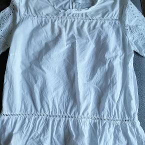 Hvid bluse i bomuld. Har broderi anglaise ved ærme samt gul mønster og flæse.