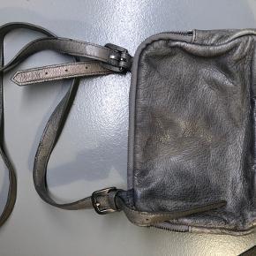 En skøn taske i fed , blød skind . Tasken har 3 rum med lynlås og een under klappen .  Regulerbar strop . Str 22 x 17 .