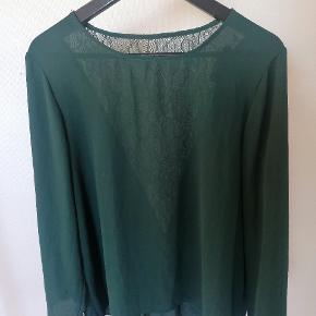 Mørkegrøn bluse med blonde detalje på ryggen. Har aldrig været brugt