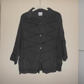 """Vældig smart skjorte fra in Front med en masse detaljer og 3/4 ærmer.    Mørk grå. Str. M. Brystvidde 104 cm, længde fra nakken og ned 62 cm. 97% bomuld, 3% elastan.    Det var desværre et fejlkøb. Så den er """"ny"""" og aldrig brugt, men den har dog været vasket forsigtigt.    Køber betaler gebyret ved evt. TS-handel.    Mvh.  Skjorte Farve: mørk grå Oprindelig købspris: 500 kr."""