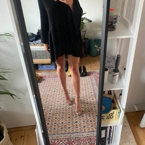 Flot og elegant kjole med plisseret skørt og ærmer.