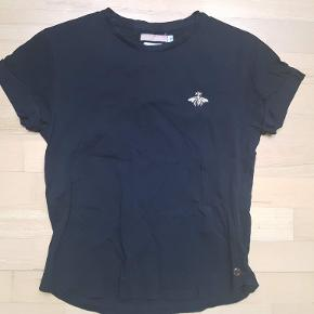 Sort t-shirt fra Birgitte Herskind med en lille broderet bi ved brystet og opsmøg ved ærmerne. Ingen synlig slitage.