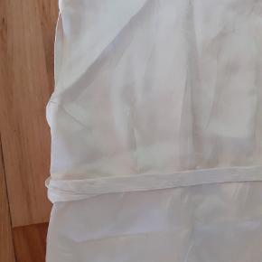 """Brudekjole fra 1958  Farven er knækket hvid.   Fin Brudekjole fra 1958 sælges. Den er syet til bruden, så jeg er ikke sikker på størrelsen.  Kjolen er i generelt meget god stand, men er gammel, har lidt smuds/lugt og skal vaskes eller renses. Båndet under bryste skal hæftes fast. Men ellers er der ikke noget som skal syes. Der var oprindeligt et slæb som kunne hægtes på kjolen, man kan lave et nyt, hvis man er kreativ..  Men kjolen er flot som den er.  Jeg har taget målene liggende og ganget op hvor det giver mening.  Bryst (taget målt fra armhulen) er der 88 cm hele vejen rundt.  """"Taljen"""" som på kjolen er lige uden brystet er 78 cm... Det er der hvor din bh strop sidder.... Herfra går kjolen ud i en lige linje og jeg vurderer at den er små 90cm i taljen.... Men det er min vurdering!   Længden er fra skulder søm til gulv 136 cm foran og 138 bagpå."""