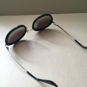Runde Prada solbriller af modellen SPR 50TS i str. 54. Graduerede solglas. Aldrig brugt, men har varme skade under højre glas (ujævnhed i acetaten).  Gucci etui i sort velour medfølger.