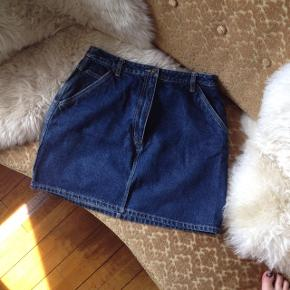 Kort Denim nederdel i klassisk mørkeblå.  Har lommer + mange fine detaljer (flere end ses på billedet) og sidder super flot slankende 😍  Tag. Cowboynederdel