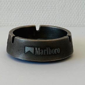 Ikoniske Marlboro har været i handlen siden Phillip Morris i 1902 åbnede en butik i New York. Her kan du få del i historien :-)  Diameter: 11 cm Højde: 3,5 cm Fremstår med brugsspor i bunden - se billede.