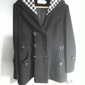Flot sort uldjakke, med aftagelig hætte, str. Ca. 42/44, brystvidde 112 cm, længde 70 cm. Brugt få gange.  Uld jakke Farve: Sort Oprindelig købspris: 599 kr.