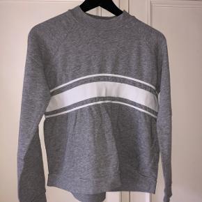 Lysegrå sweatshirt med hvide streger over maven