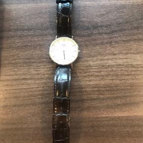 Daniel Wellington ur med brun slangeskindsrem og guldskive, 3,5 cm i diameter.  Brugt. Ingen store ridser i glasset. Brugstegn på rem. God stand.