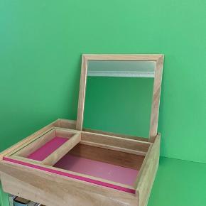 Stor nomess opbevarings kasse i lyst træ og lyserød.  Den har vendbart spejl som også kan bruges til låg.  Den har to fejl, en lille plet i bunden og en solskade på låget