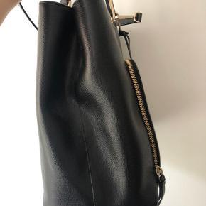 Mål: H: 28 cm B: 33 cm for oven og 39 for neden D: 15 cm  Tasken er af ægte læder og uden skrammer. Den er virkelig rummelig da der er to store rum (der kan være en lille laptop) et lynlåsrum foran samt to indeni plus to små lommer på indersiden.  Remmen kan tages af så tasken kun har to små hanke.
