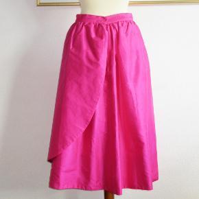 Skræddersyet: Exclusiv Ægte thai-silke  100 % Thai-silke:  Super flot nederdel i asymetrisk snit og med stor (aftagelig) blomst. Vildt fantastisk nederdel. Nederdelen er med foer.   Livvidde: 37 cm x 2 Længde: 80 cm  Ingen byt, og prisen er fast.
