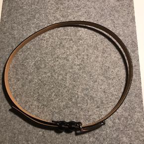 Sælger dette klassiske sorte bælte fra Tiger of Sweden. Så kun begrænset tegn på slid. Bæltet er smalt og måler 2 cm. Måler 90 cm. Langt.