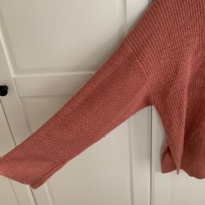 Lyserød/rosa H&M sweater med slits i siderne og let oversize ærmer. 70% akryl, 30% uld.