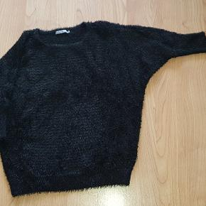 Pæn trøje i sort med korte ærmer. Smart med en bluse under. Måler over bryst CA. 120 cm Længde fra hals og ned CA. 120 cm