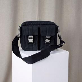 Super fed taske fra RE:DESIGNED med mange lommer og rum 🤩💛 den har sølv detaljer og en bred rem ! Den er som ny, kun brugt max 2 gange 😊 BYD   Materiale: 100% nylon Mål: H: 18 x B: 24 x D: 6 cm