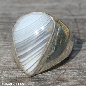 Brand: New Yorker Sølv Varetype: Unik Ring I Sølv Med asymetrisk skåret botswana agat Størrelse: 53½ Farve: Se Foto Prisen angivet er inklusiv forsendelse.  Unik ríng hjemtaget fra New York. Den er lavet i sterling sølv med en indfatning af en asymetrisk skåret poleret botswana agat. Selve stenen måler 21x15 mm på de bredeste ledder.  Disse smykker er ikke serieproducerede og jeg har kun denne ene ring i denne størrelse, så derfor sælges de efter først-til-mølle-princippet.   Botswana agat er en rigtig lykkesten, den bringer dig uventet glæde, den styrker din jordforbindelse. Den er god når du har brug for at være tilstede, når der skal træffes vigtige beslutninger. Derudover er en Botswana agat en meget healende sten i alle sammenhænge. Den er stærk, men den kan samtidig være blid - hvad den er for dig, afhænger af, hvad du for øjeblikket går og tumler med. Har du brug for et blidt puf for at komme videre på din spirituelle vej, er en Botswana agat nærmest et must for den hjælper dig til at se, hvilken retning, du kan gå i, uden at forstyrre din beslutningstagen på nogen måde. Bær en Botswana agat på kroppen og du vil føle, at tingene løser sig op for dig, på alle niveauer.   Prisen er fast, og det sælges til den første der trykker på køb-nu-knappen, eller byder prisen.  Check gerne min profil og se om der skulle være mere som falder i din smag.  Bemærk venligst at jeg ikke bytter med andre varer, beklager.  Prisen inkluderer forsendelse som brev med Postnord.