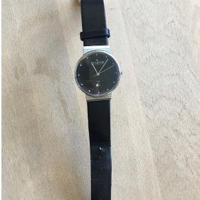 Skagen ur med sort rem, sølvkant og sort urskive.