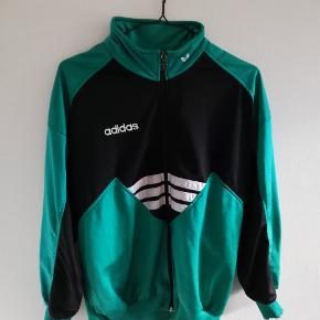 Vintage Adidas trøje fra 90'erne. Er i super stand, bortset fra et lille bitte hul/brændemærke på højre ærme - se billede 3. Købt brugt (med hul!) i Urban Outfitters for 650 kr.