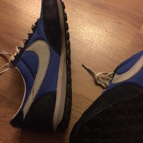 Slidt ved hælen indvendigt og på siden der vender indad (se billede 2)