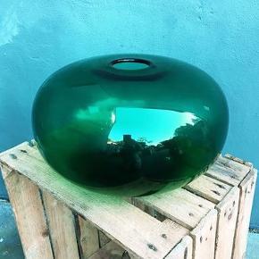 Enormt flot stor dyb blågrøn vase i solid glas. Jeg har desværre ikke rigtig plads til den så den sælges til højst bydende.  Har en rids fra flytningen på den ene side, hvilket ikke ses hvis vasen vendes om. Jeg husker desværre ikke hvor den er fra - har haft den i nogle år. Mindstepris 200kr.  Højde: 18 cm Diameter 31  Kan afhentes i Horsens el. fragtes til Aarhus efter aftale