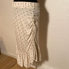 Lækker og let nederdel med mørkerøde prikker, med skøn deltaljer.