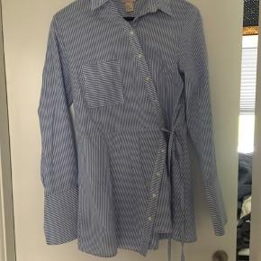 Asymmetrisk skjorte med bindedetalje. Ingen skader.