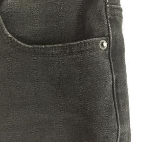 Cowboynederdel med lommer for og bag, lynlås og knap. Kort slids bagtil.