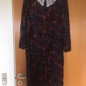 Smuk 80'er retro / vintage blomstret kjole med en hvid blondekravd, som passer en str. 38. Ved ikke hvad materialet er, men det er en blød og behagelig kvalitet. Lomme i den ene side. Spørg efter mål.
