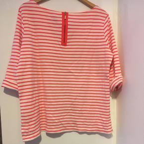 Fin bluse med pink striber og lynlås bagpå. I kraftig bomuldskvalitet.