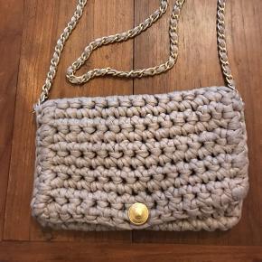 Super fin hæklet taske med lang guld kæde.  Farve: sand  Mål: 17 X 27 NP: 999.-