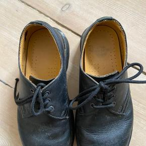 De klassiske sorte Dr. Martens docs / sko / de lave sko med gule stikninger.  De har givet sig og vil sige de passer en str. 37.   Docsne er behandlet med læderfedt så de holder ekstra godt (det er det der kan ses på overfladen, man kan godt massere det pænere ud).   Se billeder for standen.   Kan afhentes i 2200 eller sendes mod betaling af fragt.   Foretrækker mobilepay som betaling. Handler også via TS såfremt køber betaler alle gebyrene.
