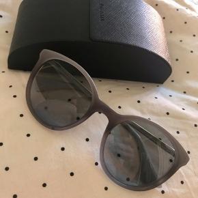 Super fed Prada solbrille i grå nuancer. Kun brugt meget lidt, da jeg har for mange andre solbriller at vælge imellem 😋 Godt hårdt etui medfølger. Kvittering haves ikke, da den er købt gennem arbejde.