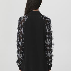 Denne skjorte med fjerudsmykninger er fremstillet af en lækker silkeblanding og forsynet med en åben halsudskæring samt en fin skjortekrave. Den lette style er et elegant valg både til hverdag og fest. Materiale: 50% silke, 50% polyester. Mål str. 32: bryst 49cm, længde 65,5cm, ærmelængde 82cm, bundvidde 49cm.  Nypris: 3.200kr.