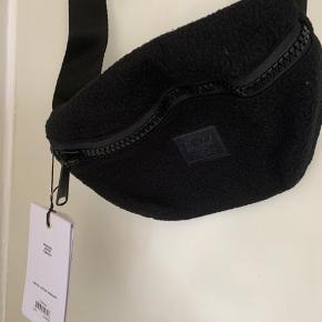 Sort unisex bæltetaske / crossbody i teddy / sherpa med lang regulerbar rem. Model Fourteen (et rum) Mål ca 20 cm bred og 15 cm høj
