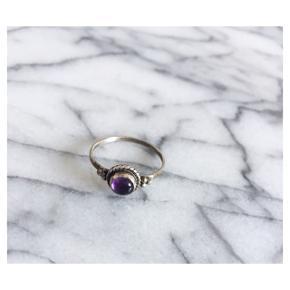Lille ring (mit bud er den svarer til en størrelse xs) købt brugt. Sølvfarvet med en lille lila sten. Sender gerne med DAO :)