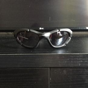 """Super fede 90'er. vintage Oakley solbriller, sælges..    Sælger de her mega fede 90'er vintage Oakley solbriller, i et ret heftigt design..    De kommer fra en gammel nedlagt sportsbutik der har haft dem gemt væk på dit lager, i ca 15-18 år..    De er """"NOS"""" hvilket vil sige : New old stock / Ny gammel lagervarer, og derfor i 110% ny stand!    Sælges incl Dustbag..    De er desværre blevet beskadiget, og det ene glas, er derfor blevet ridset godt og grundigt,og skal derfor skiftes..    Sælges derfor også ekstremt billigt, pga ovenstående..    Få nogle super fede og yderst moderne solbriller til sommeren, de færreste har (endnu...)    Ift til hvad nypriserne på lign Oakley solbriller ligger på i snit på nettet, tænker jeg at min mp på 250.kr, er mere end fair! - De er sat ca 50% under dagens markedspris, for lign briller..    Skulle der være rift om dem, ryger de til højestbydende, og ydermere sælges de også på tradono, og G&G.. De skal nok ryge hurtigt, så slå til, imens  tid er..     SE OGSÅ ALLE MINE ANDRE ANNONCER.. :D"""