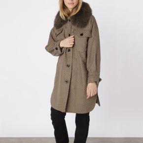 Lang skjortejakke i bomuldskvalitet med aftagelig krave i pels af blåræv inspireret af vores tidsløse  'charlie jacket'. Jakken har knaplukning fortil samt to brystlommer.   Jakken er en S/M   Brugt 1 gang.   Kvittering medfølger.
