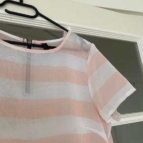 Rigtig fin gennemsigtig tshirt i en sart lyserød og hvid stribet farve.   Der er en lynlås på ryggen.  Størrelse M (passes dog også af en S).  Næsten ikke brugt.  Spørg endelig efter flere billeder. Mængderabat gives ved køb af flere dele.  Sender gerne på købers regning.