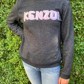 Kenzo sweat i en let gråmeleret kvalitet med lyselilla & hvid aplication. Det er en voksen str. L, men da de er små i str. svarer det til str. XS-S NYPRIS ca.1400,- Obs! Der er en lille plet i lilla akrylmaling foran det kun anes, derfor er den billig