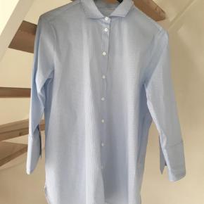 Varetype: Helt ny skjorte Farve: Lyseblå Oprindelig købspris: 500 kr.  Lækker helt ny klassisk stribet skjorte fra Second Female.     Skjorten har almindelig skjortekrave og trekvarte ærmer med brede dobbelte manchetter, som giver skjorten lidt ekstra kant. Afrundet kanter forneden og lille slids i siderne.    Kvalitet: 64% Bomuld, 32% Polyamid, 3% Elastan