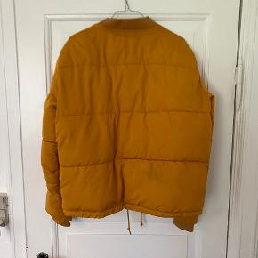 Flot karrygul bomber jakke/vinterjakke i dynejakke stil, super fin og varm. Har lommer og lynlås + trykknapper. Har et lille hul bagpå skulderen, derfor prisen🌟