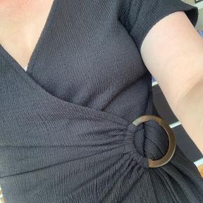 Sort kjole med flot detalje i livet. Passer også en 42.   Fejler intet!