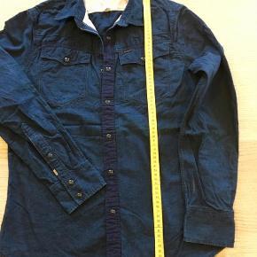 Varetype: Langærmet Farve: Blå  Mørkeblå denimskjorte, kun brugt een gang.  Armlængde fra armhule og ned er ca 49 cm.