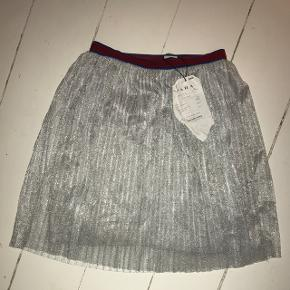 Sød glimmer nederdel med et virkelig fint bånd i toppen. Swipe for flere billeder!Aldrig brugt, som man også kan se på 2. billede. Stadig med kvittering og prismærke! (Perfekt nederdel til nytårsaften!) NP : 139kr