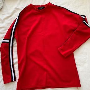 Fin rød bluse med sorte og hvide striber på ærmerne 😊