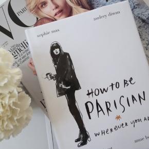 """Bog """"how to be parisian"""". Fin stand. Kan ses at den har stået en smule i lys. Ellers fejler den intet."""