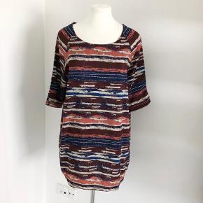 Sød kjole fra Pulz i brændte farver som koral, blå, brun og råhvid.  Bred udskæring.  Ærmerne lukkes med to knapper og er 3/4 lange.  Kjolen går ind i en fast linning forneden, så den ikke flagrer, når man bevæger sig.  Længde fra skulder er 90 cm, og brystmålet og taljen måler 112 cm.  Fremstillet i tynd polyester.  Bærer ikke præg af brug.